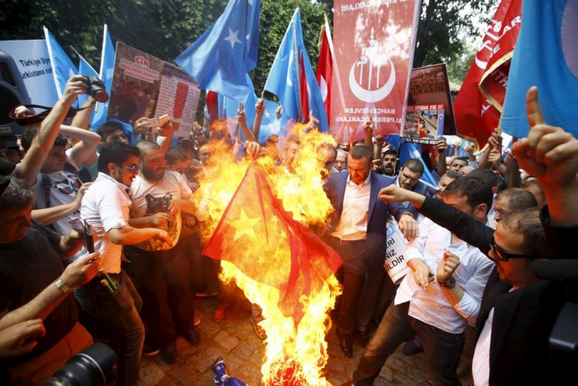 Demonstrators set fire to a Chinese flag during a protest against China near the Chinese Consulate in Istanbul, Turkey, July 5, 2015. REUTERS/Osman Orsal